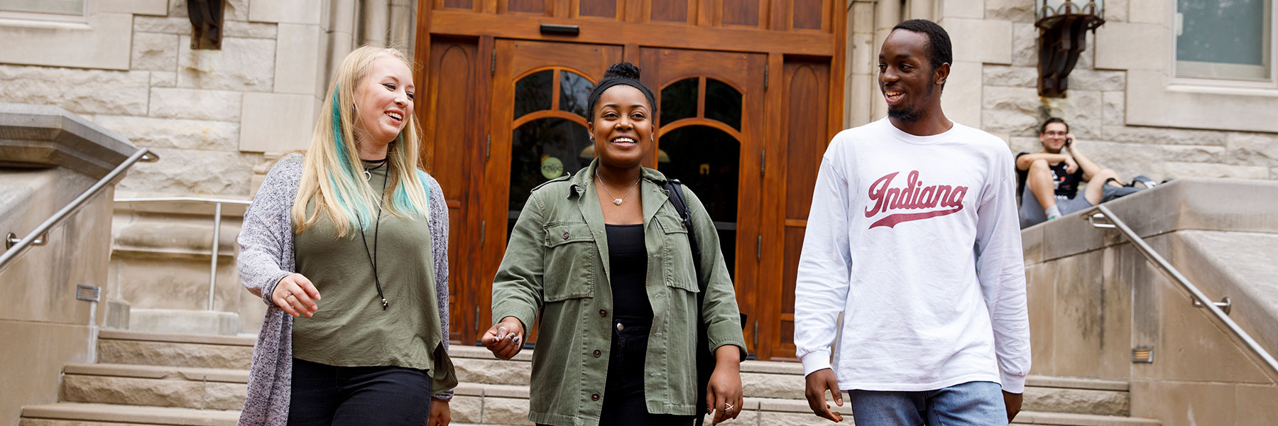 Three students walking in front of the entrance to Franklin Hall.