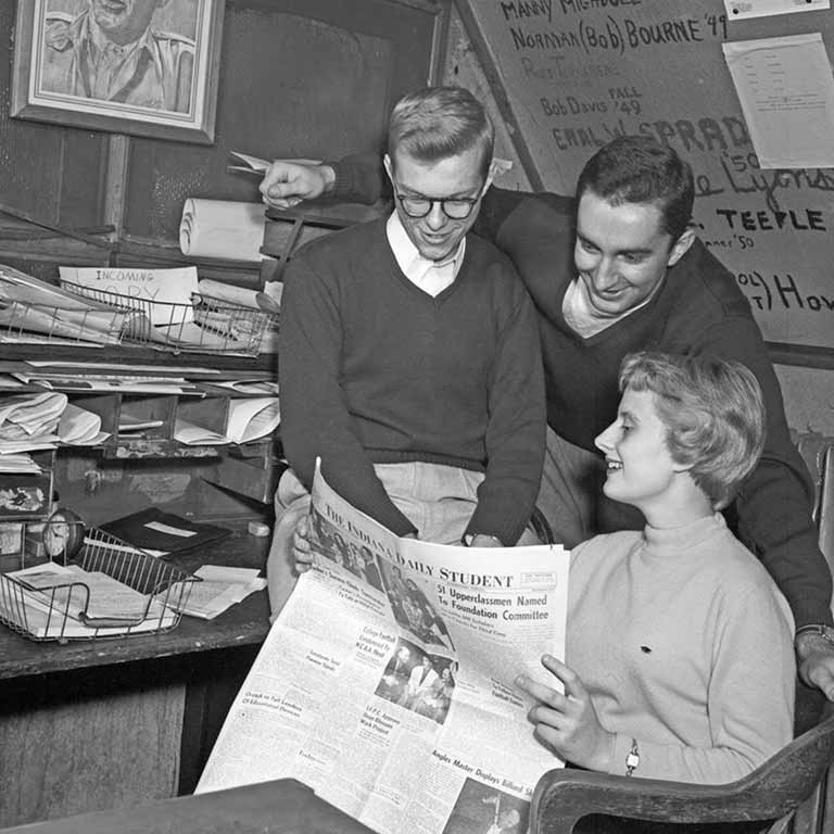 Three students read a paper at the Indiana Daily Student office in 1953.
