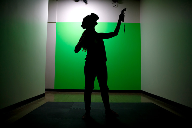 A student stands in front of a green screen with a virtual reality headset and controller.