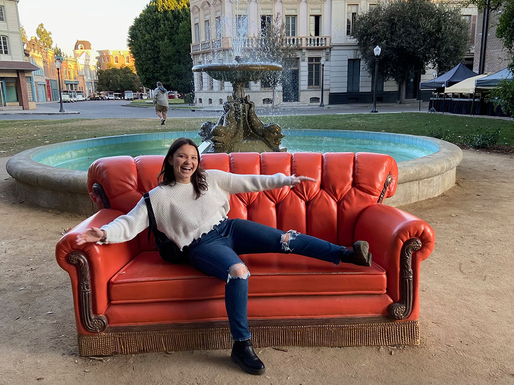 A student sitting on the 'Friends' couch at Warner Bros. Studios.
