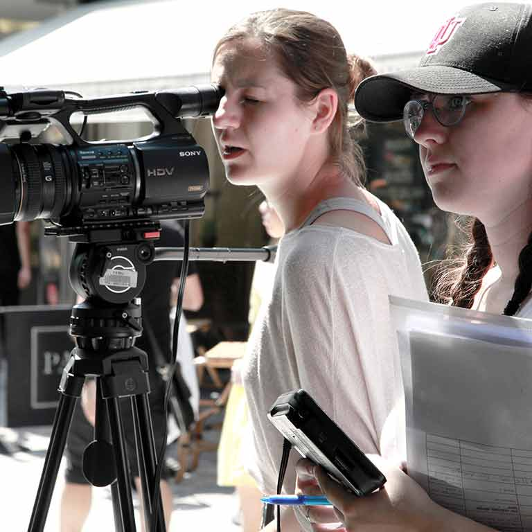 Two students practice motion picture production using a video camera and script.