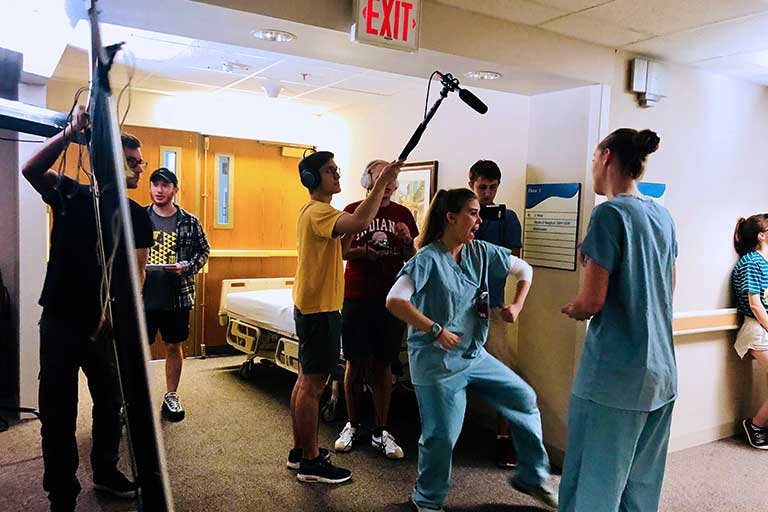 Student filmmakers carry equipment and record video of actors dressed in scrubs.