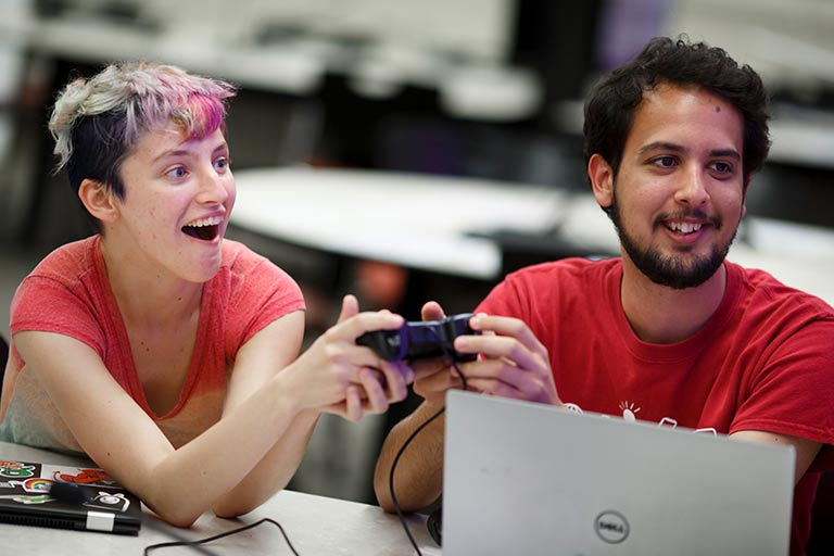 Two students interact with a game controller and a laptop at a student club event.