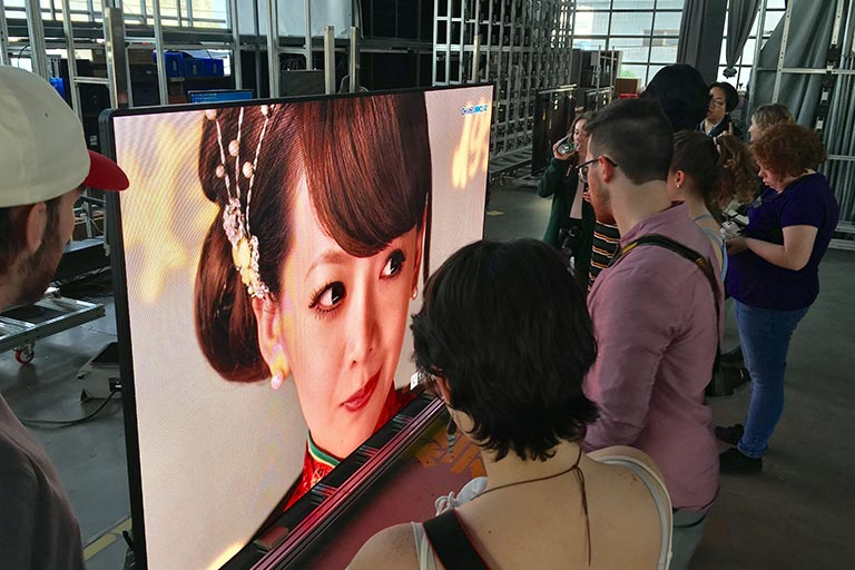 People stand around a screen showing a woman in Chinese traditional dress during a student show.