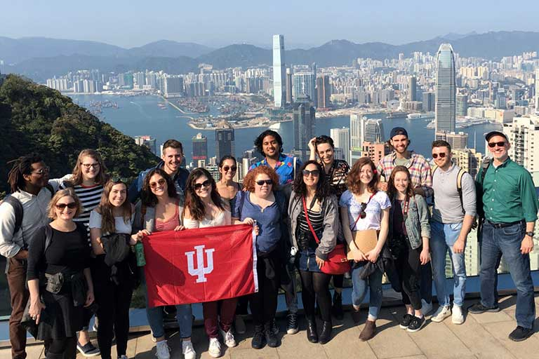 A student group poses in front of a cityscape during a field experience course in China.