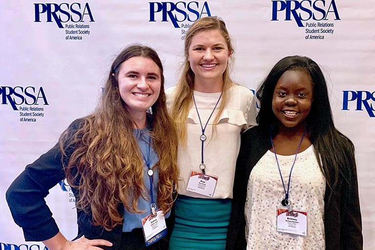 Three students pose while at an Public Relations Student Society of America event.