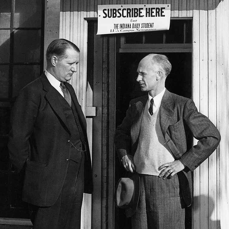 Ernie Pyle talks with a man in a suit in front of a doorway and sign to subscribe to the IDS.