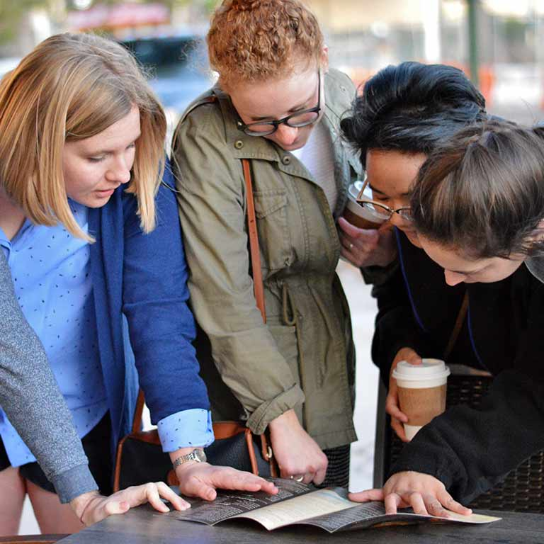 A group of students look at a brochure during a student trip.