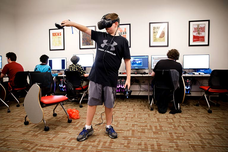 A Game Development Camp participant plays a virtual reality game in a computer lab.
