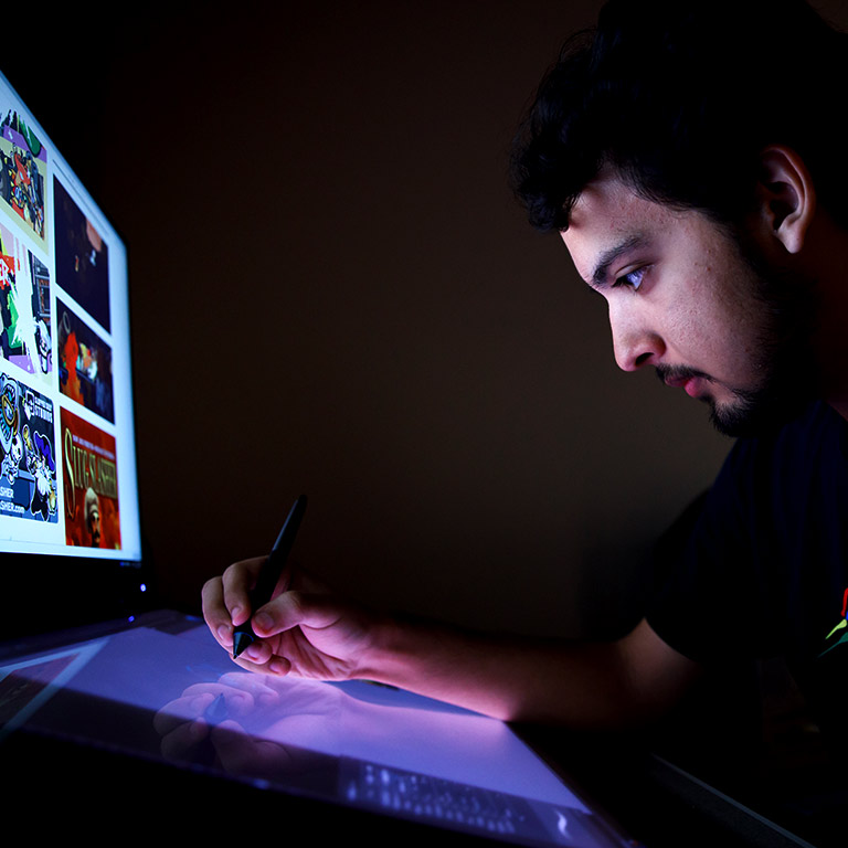 A student draws on a drawing tablet as he looks at a design on a monitor.