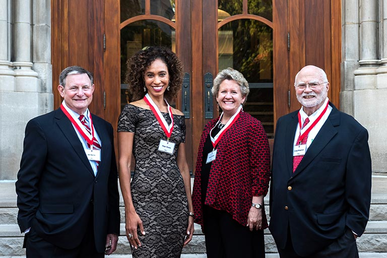 Three 2018 Distinguished Alumni Award winners stand with their medals in front of The Media School.
