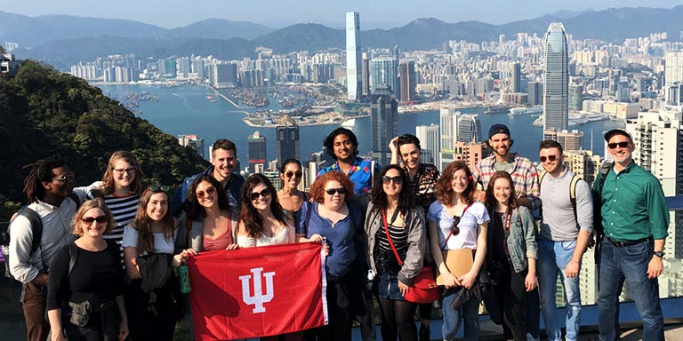 A group of students hold an IU flag during a trip with the Hong Kong cityscape in the background.