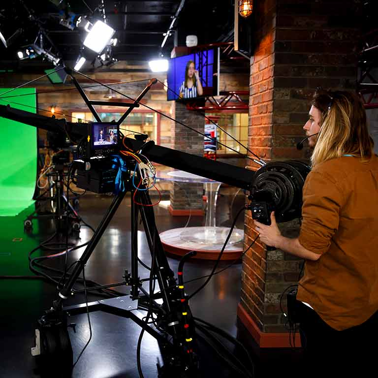 A student operates a large camera on a TV set.
