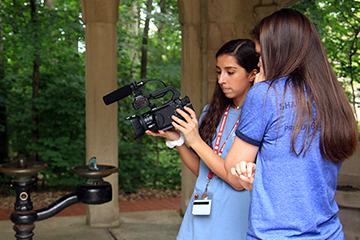 Two students use a video camera to record a fountain in Dunn's Woods.