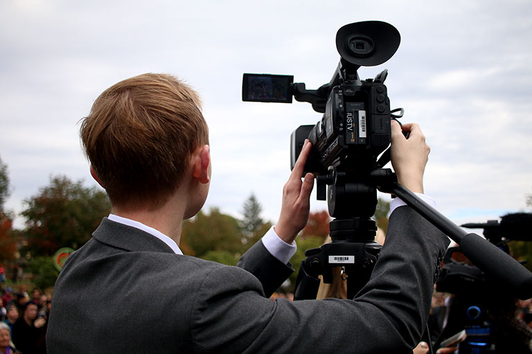 A student in a suit uses a video camera outside.
