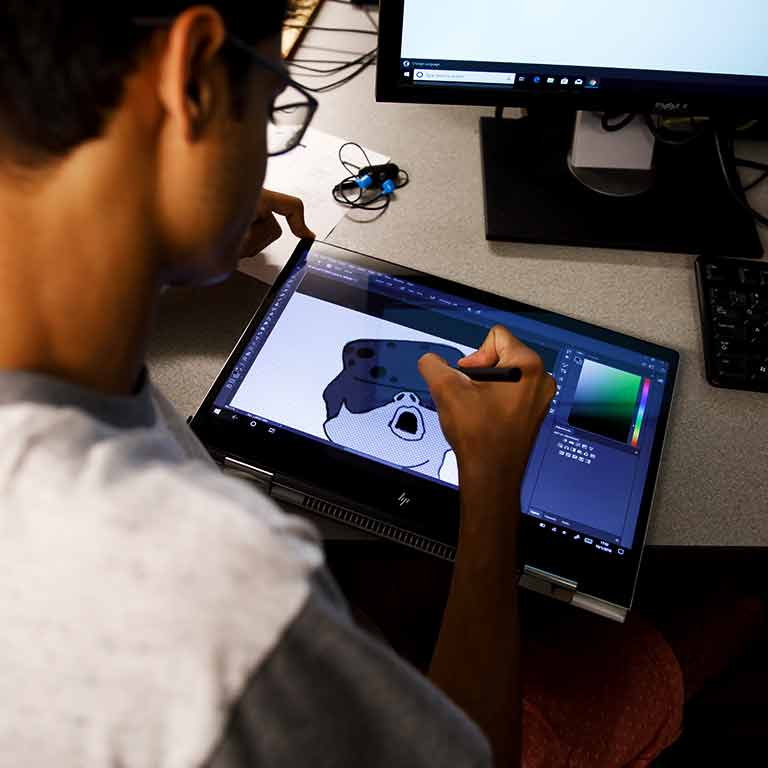 A student uses a writing tablet to make a design.