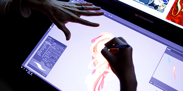 A student's hands as they work on a design on a writing tablet