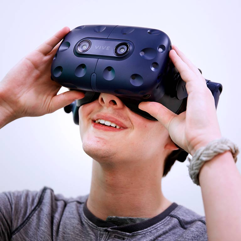 A student looks into a set of virtual reality goggles.