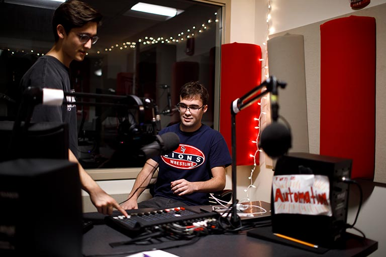 Two students work with sound equipment in a production studio space.