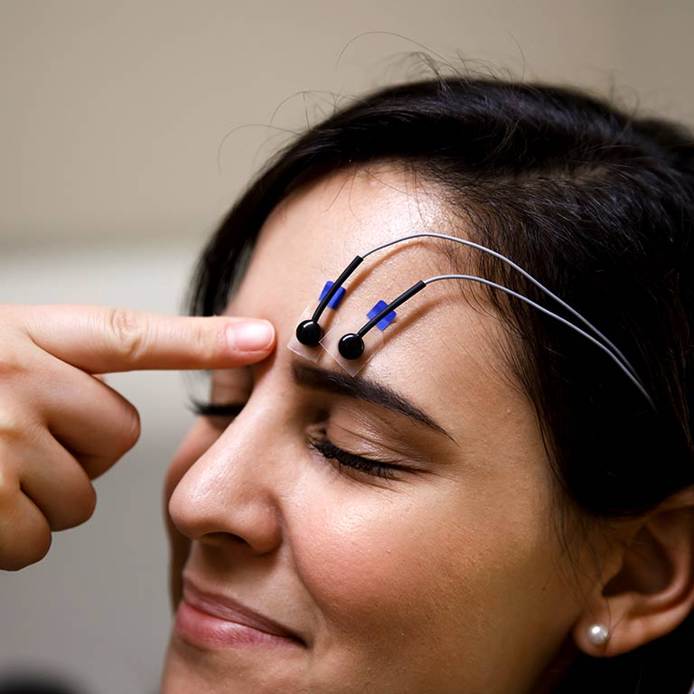 A researcher's hands putting electrodes on a participant's head