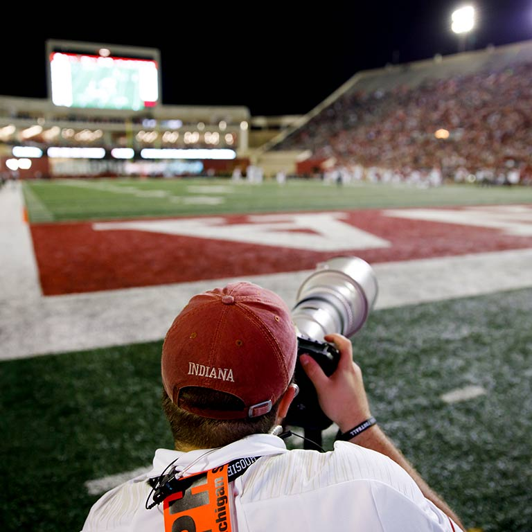 A student takes photos with a long range lens at a football game.