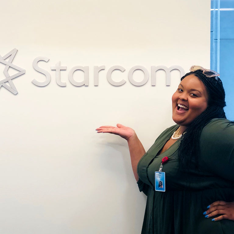 Aubrei Hayes stands in front of a sign for Starcom in Chicago.