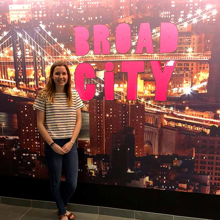 Sarah Opinsky stands in front of a sign for Broad City in New York City.