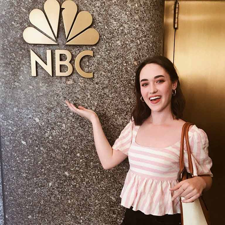 Maia Rabenold stands in front of a sign for NBC in New York City.