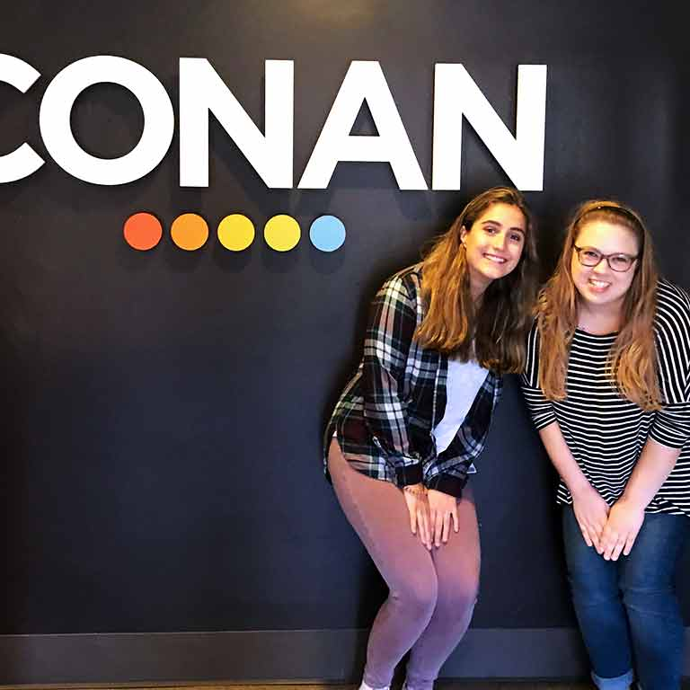 Two students stand in front of a sign for Conan for their Semester in Los Angeles.