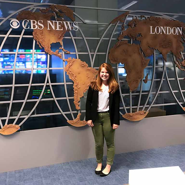 A student smiles in front of a sign for CBS London for her Summer in London.