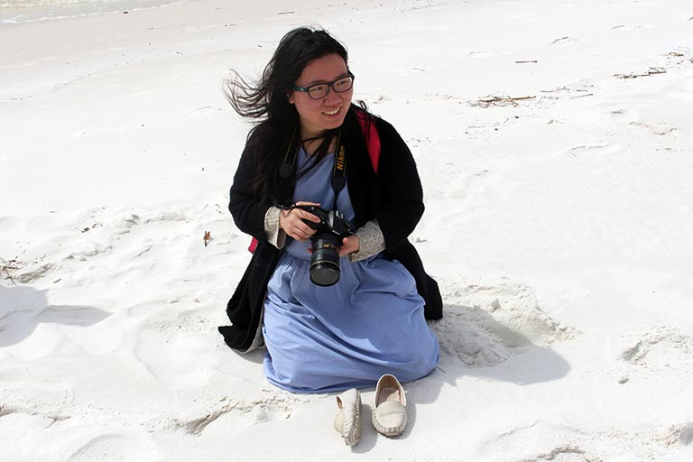 A student with a camera kneels in the sand on a beach.
