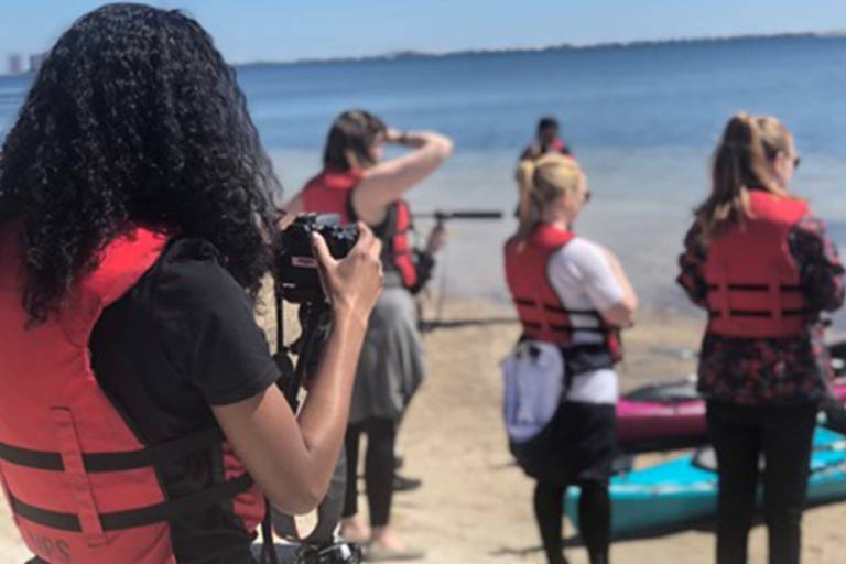 A group of students uses audiovisual equipment on a beach.