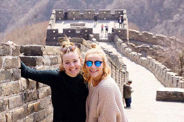 Two students stand on the Great Wall of China.