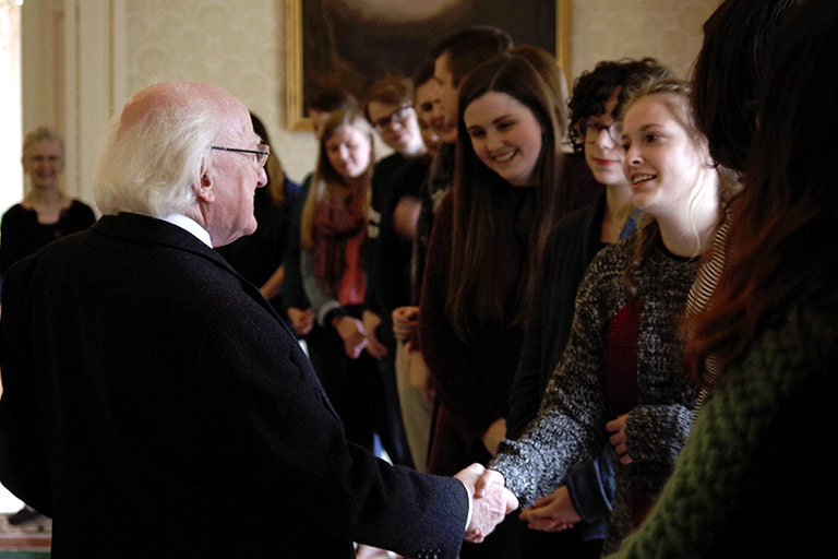 A group of students waits to meet and shake hands with a man in Ireland.