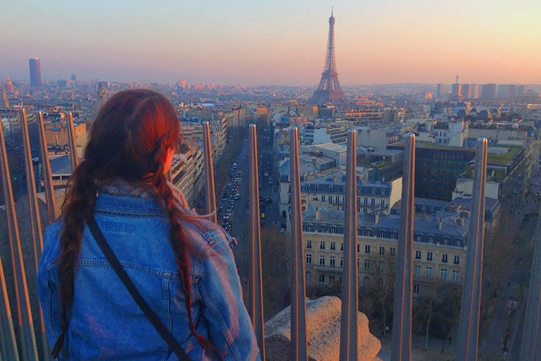 A woman looks out over Paris in the direction of the Eiffel Tower at sunset.