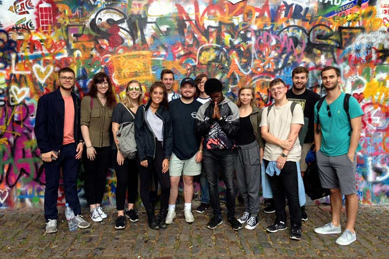 A group of students stands in front of a wall covered in graffiti.