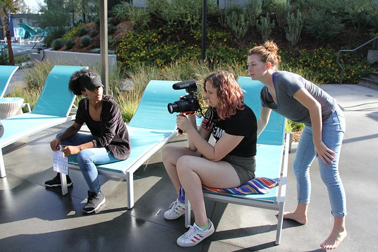 A group of students looks through a camera to plan out a shot.