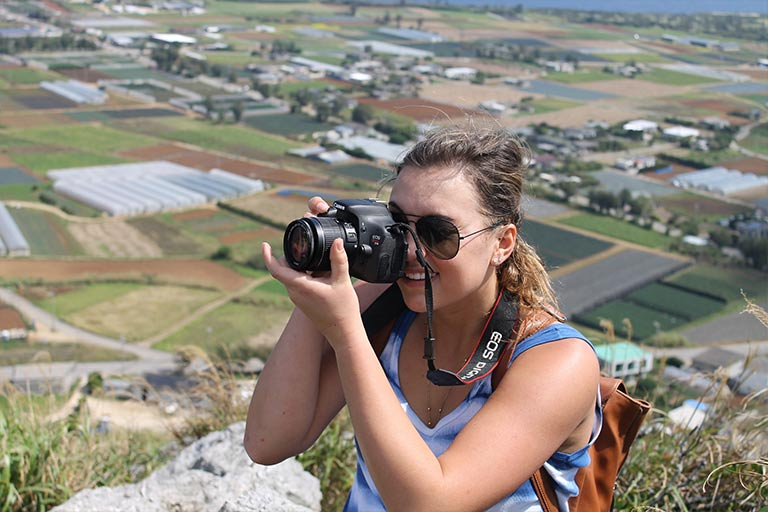 A woman takes a photo standing on a hillside above a valley.