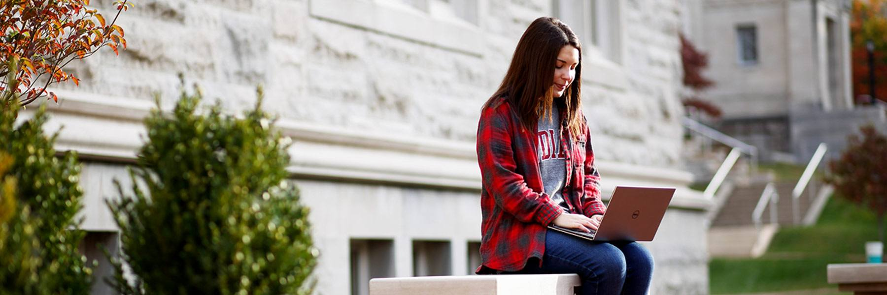 A woman sits on a stone bench outdoors and uses a laptop.