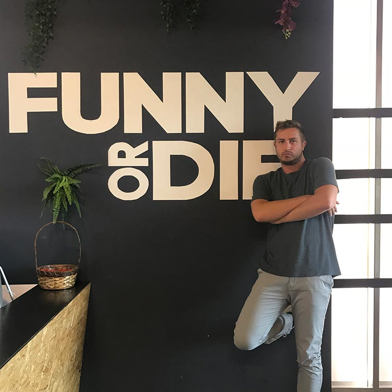 A man leans against a wall that with the words 'Funny or Die.'