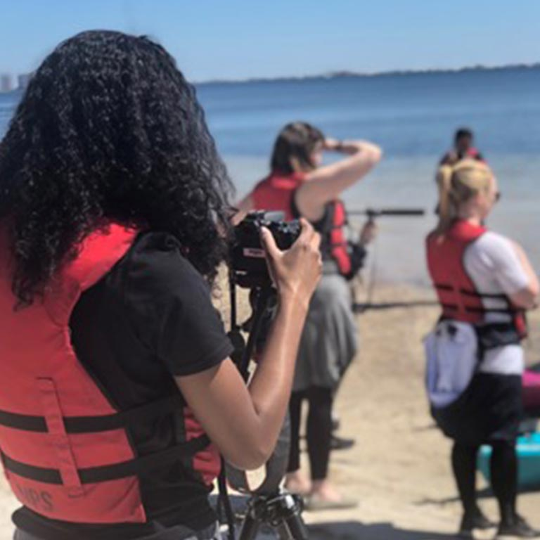 A group of students use audiovisual equipment on a beach.