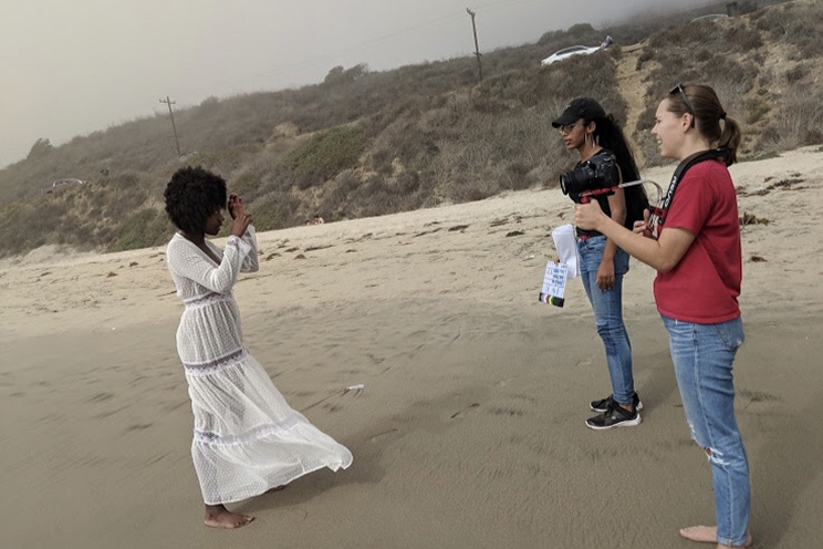 Students stand on a beach with a camera and plan out a shot.