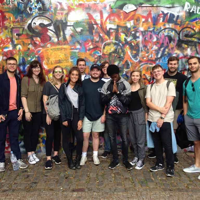 A group of students stand in front of a wall covered in graffiti.