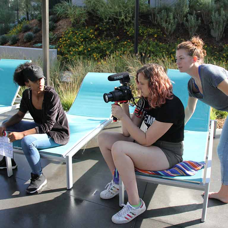 A group of women evaluate a shot through a camera.